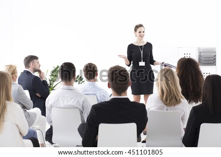 Young beautiful successful employer and her team having a business meeting in a conference room - stock photo