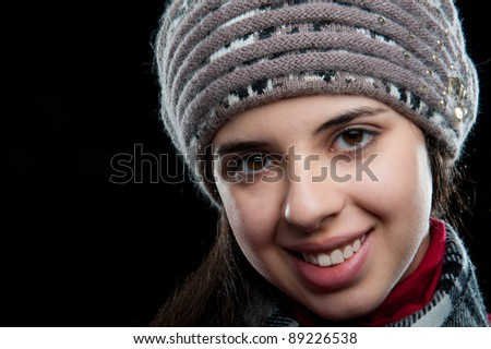 young beautiful sweet attractive girl in a red sweater in a gray hat and a scarf on a black background