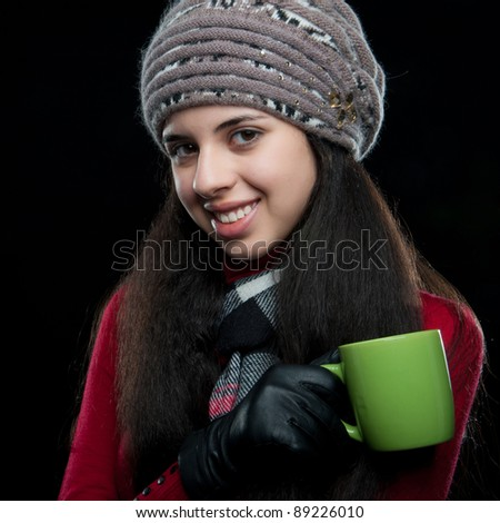 young beautiful sweet attractive girl in a red sweater in a gray hat and scarf holding a green cup in hand, isolated over white