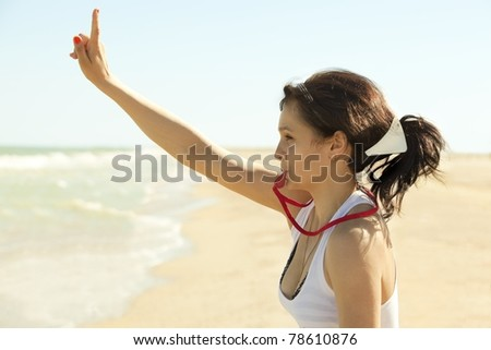 Young beautiful swimmer training attracting attention and blowing the whistle outdoors - stock photo