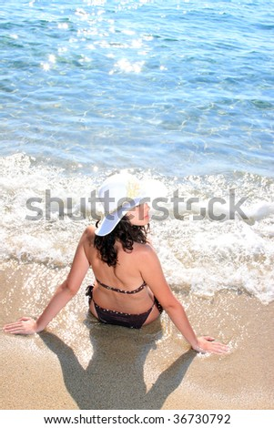 Young beautiful tanned woman in bikini in the sea