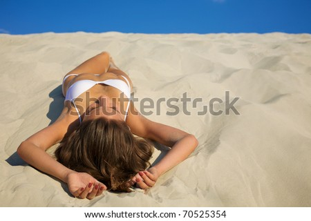 Young beautiful tanned woman laying on sea beach - stock photo