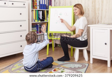young beautiful teacher involved with a student at the blackboard. The woman shows the board, looking at the student, smiling. Pupil sitting on the floor, raised his hand