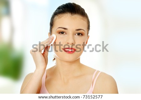 Young beautiful teen caucasian woman using a cotton pad to remove her make-up. - stock photo
