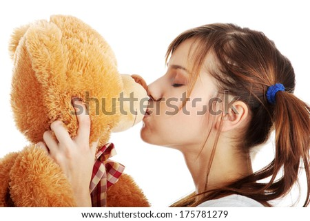 Young beautiful teen woman in long shirt with her teddy bear, isolated on white background - stock photo