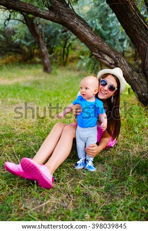 Young beautiful teenage girl and baby boy sitting on green grass. Older sister and little brother. Happy children, kids on a nature meadow in the park. Portrait of smiling family outdoors. - stock photo