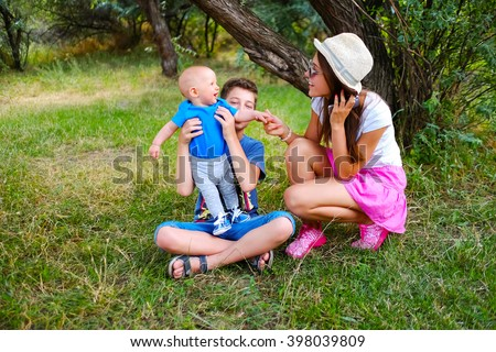 Young beautiful teenage girl and boy and baby boy sitting on green grass. Older sister and little brother. Happy children, kids on a nature meadow in the park. Portrait of smiling family outdoors. - stock photo