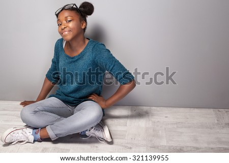 Young beautiful teenage girl sitting on the floor. Girl with eyeglasses on head looking at camera, smiling. - stock photo