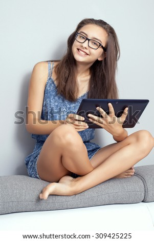 Young beautiful teenage girl sitting with tablet at home, learning. Smart girl with beautiful smile. - stock photo