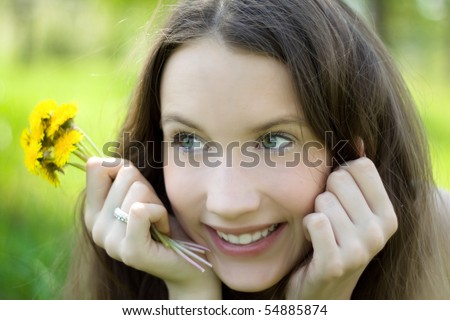 young beautiful teenager with dandelion bouquet smile - stock photo