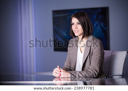 Young beautiful television announcer at studio during live broadcasting.Transmission with serious smiling journalist woman.Television anchorwoman at studio during live broadcasting