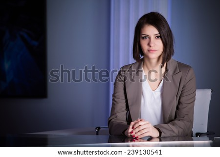 Young beautiful television announcer at studio during live broadcasting.Transmission with serious smiling journalist woman.Television anchorwoman at studio during live broadcasting - stock photo