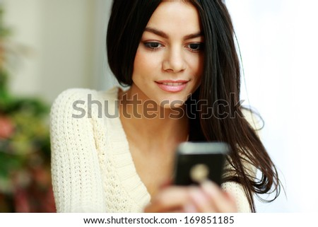 Young beautiful thoughtful woman using smartphone at home - stock photo
