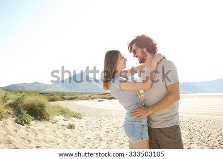 Young beautiful tourist couple enjoying a summer holiday on a destination coast on a sunny vacation together, hugging with joyful expressions, sandy beach outdoors. Travel and honeymoon lifestyle. - stock photo