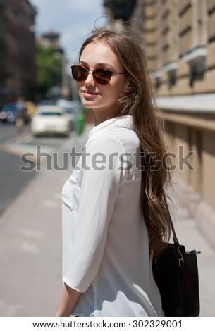 Young beautiful tourist girl walking on summer street. - stock photo