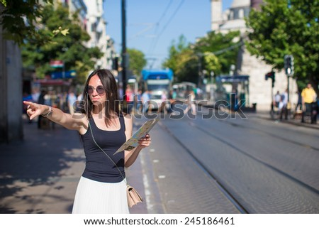 Young beautiful traveling woman with map in the city - stock photo