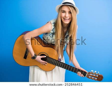 Young beautiful, trendy girl with acoustic guitar is posing on blue background. - stock photo