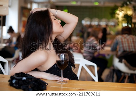 Young beautiful trendy woman in the bar. Beautiful Asian girl in a pub. Woman with alcohol.  - stock photo