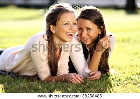 Young beautiful twins of sister lays on green field - stock photo
