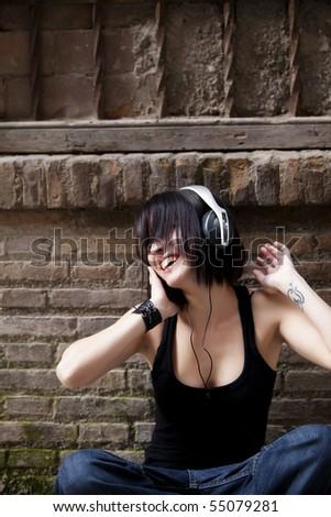 Young beautiful urban girl enjoying music - stock photo