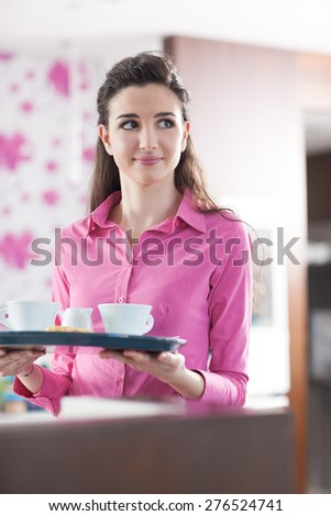 Young beautiful waitress at the cafe serving coffee with a tray - stock photo