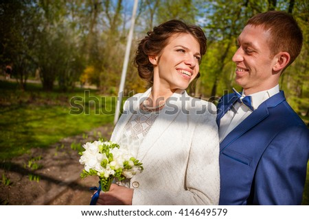 young beautiful wedding couple in the spring park. Smiling and happy