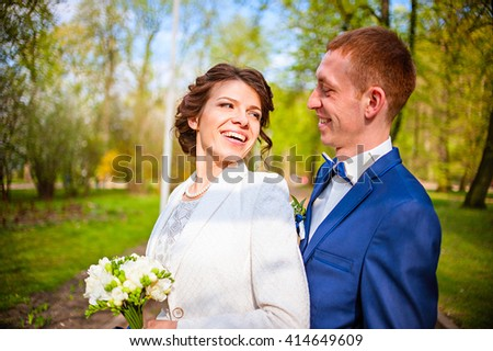 young beautiful wedding couple in the spring park. Smiling and happy - stock photo