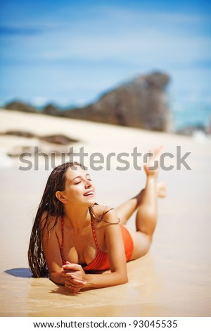 Young beautiful wet woman lying on the sand near ocean, Bali, Indonesia