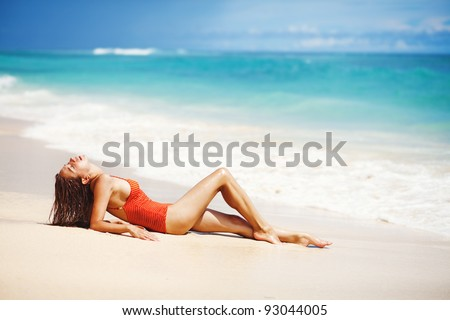 Young beautiful wet woman sitting on the sand near ocean, Bali, Indonesia
