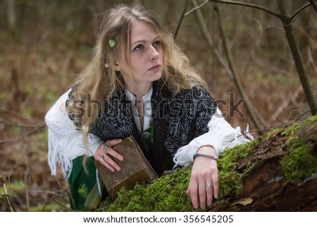 Young beautiful witch in the woods - stock photo