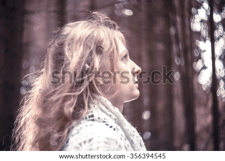 Young beautiful witch in the woods, soft focus - stock photo