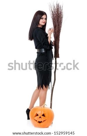 Young beautiful witch with broom and pumpkin over white background