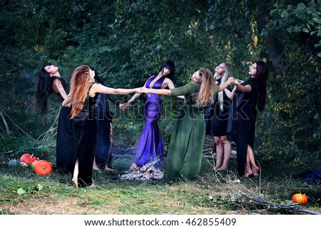 young beautiful witches dancing in the forest holding hands