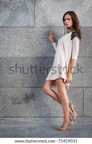 Young beautiful woman against a stone wall - stock photo
