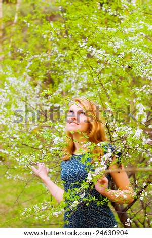 Young beautiful woman and blossomed tree - stock photo