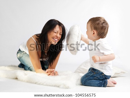 Young beautiful woman and her son having fun together - stock photo