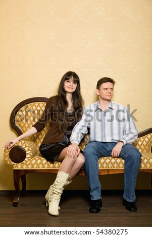 young beautiful woman and man sitting on sofa in room, man has put hand on knee to girl - stock photo