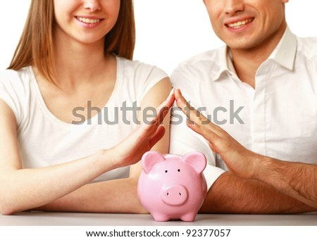 Young beautiful woman and man with piggy bank (money box), isolated on white background - stock photo