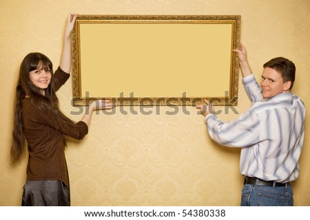 young beautiful woman and smiling man hang up on wall picture in frame - stock photo