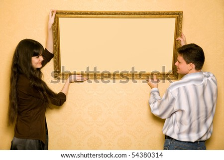 young beautiful woman and smiling man hang up on wall picture in frame, looking at picture - stock photo