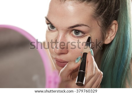 young beautiful woman applied concealer under her eyes - stock photo