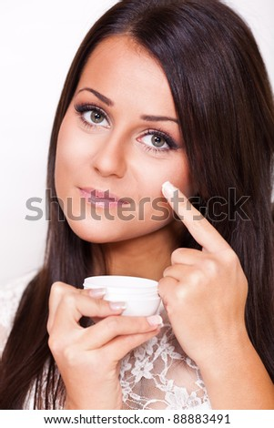 Young beautiful woman applied face cream - stock photo