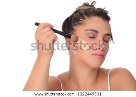 young beautiful woman applied makeup with a brush