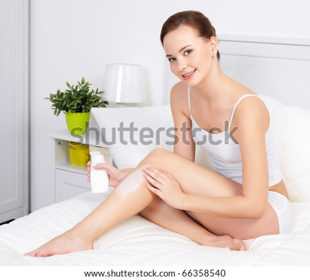 Young beautiful woman applying cream for skin on legs - indoors