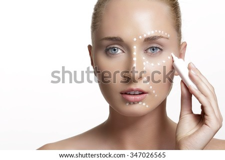 young beautiful woman applying creme on her skin on white - stock photo