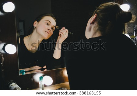 Young beautiful woman applying her make up face with brush, looking in a mirror, sitting on chair at dressing room with vintage mirror dark room - stock photo