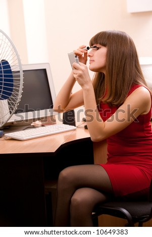 young beautiful woman applying make-up at office - stock photo