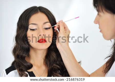 Young beautiful woman applying make-up by make-up artist - stock photo
