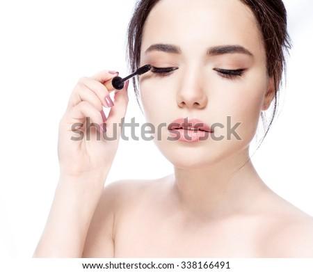 Young beautiful woman applying mascara makeup on eyes by brush - stock photo
