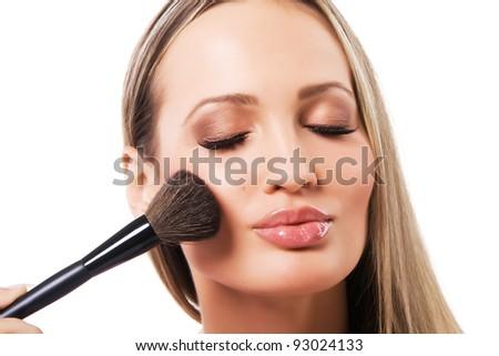 Young beautiful woman applying powder - stock photo